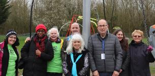 Decorative image showing members of the Nevendon Neighbourhood Association, Cllr David Harrison (centre-right, grey jacket) and Basildon Council staff with the specialist swing unveiled for all kids in Wickford