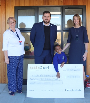 Decorative image showing photo of Councillor Callaghan presenting staff and children from St. Teresa's Catholic Primary School with funding for a new nursery