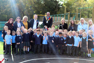 Photo of the Mayor of Basildon, David Burton-Sampson and Basildon Council senior managers with staff and children of Briscoe Primary School, celebrating their award of funding for a new classroom and outdoor space.